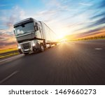 Small photo of European truck vehicle on motorway with dramatic sunset light. Cargo transportation and supply theme.