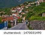 Small photo of A group of small colored houses mingled with trees seen from the top of the road in Rachoni on the Thasos island in Greece.