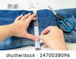 Small photo of Woman hands drawing a cut line on a blue jeans. Jeans with a large hole on a pant leg folded in half and pinned with tailor pins. Shorten the jeans. DIY shorts out of jeans.