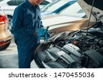 Small photo of Cropped image of mechanic in uniform wiping wrench with clean cloth after working