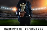Small photo of businessman holding large amount of bills at Soccer stadium in background