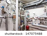 Pipes in a basement of a heating system - stock photo