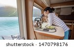 Woman in the interior of a camper RV motorhome with a cup of coffee looking at nature. - stock photo
