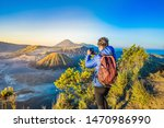 Young man meets the sunrise at the Bromo Tengger Semeru National Park on the Java Island, Indonesia. He enjoys magnificent view on the Bromo or Gunung Bromo on Indonesian, Semeru and other volcanoes