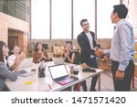 Small photo of Candid of Indian creative design man smiling and shaking hands with coworker man or colleague and other clapping hand at office workplace. Introduction to team or marketing group concept soft tone.
