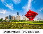 "Small photo of QINGDAO, SHANDONG, CHINA - MAY 11, 2019: ""May Fourth"" Wind sculpture in May Fourth Square with Qingdao downtown skyscrapers in the background"