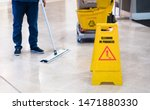 """Small photo of Janitor Cleaning Floor In Front Of Yellow Caution """"Cleaning in progress"""". Cleaning service in public area."""