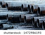 Small photo of Oil Drill pipe. Rusty drill pipes were drilled in the well section. Downhole drilling rig. Laying the pipe on the deck. View of the shell of drill pipes laid in courtyard of the oil and gas warehouse.