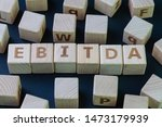 Small photo of EBITDA, Investment term Earnings before interest, taxes, depreciation, and amortization concept, cube wooden block with alphabet combine the word EBITDA on black chalkboard background.