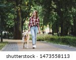 Stock photo full length view of beautiful girl in casual clothes waking in park with golden retriever 1473558113