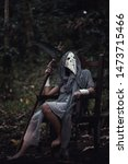 Small photo of grim reaper holding scythe sitting in the dark forest. Halloween background