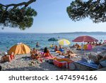 BRELA, CROATIA - July 18, 2019: Tourists enjoy the beach at Brela. The Makarska riviera in Croatia is famous for its beautiful pebbly beaches and crystal clear water. - stock photo