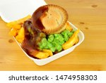 Small photo of Meat pie and chips with mushy peas in a take away box