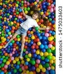 Small photo of Playground with ball pit indoor. Joyful kid having fun at indoor play center. Children playing with colorful balls in playground ball pool. Holiday or birthday.