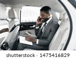 Small photo of Afro businessman arranging his affairs with notepad in the car, talking on phone