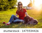 Stock photo girl in red clothing and sunglasses playing with the dog in the green grass on a sunny lawn 1475534426