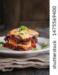 Small photo of tradicional Parmigiana di melanzane: baked eggplant - italy, sicily cousine.Baked eggplant with cheese, tomatoes and spices on a white plate. A dish of eggplant is on a wooden table