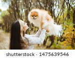 Stock photo beautiful young woman with long hair and little spitz dog 1475639546