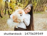 Stock photo charming young woman with little spitz dog in autumn park 1475639549