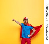 Small photo of Heroic male character dressed in superhero suit, shouts with courage I am ready to fly, makes flight gesture, saves people, makes world better place, fights against difficulties, poses indoor