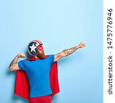 Small photo of Vertical shot of bearded man makes flying gesture, clenches fists, has goal to achieve, wears protective headgear, red cape, pretends being heroic character, has superhuman power isolated on blue wall