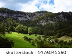 Scenic view on Jura Mountains summer green landscape in Switzerland. Meadow with sunshine, old barn, coniferous trees at the foot of the rock wall, cloudy sky. Idyllic countryside.