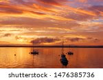 Beautiful marine after sunset background. Amazing summer evening landscape with group of drifting yachts on a lake Mendota during spectacular sunset. Bright sky reflects in the lake water.