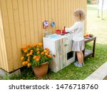 Small photo of Young girl child playing outdoors in so called mud kitchen, where you can make fake food, play with sand, dirt, water, plants and make a mess, it develops imagination and exploration.