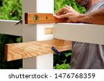 Small photo of carpentry joints. Wood post, rabbet joint. Mounting the carport. carpenter using a spirit level to connect a spruce wooden beam for Carport outdoor construction. Woodworking and carpentry concept.