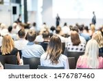 Small photo of Business and entrepreneurship symposium. Speaker giving a talk at business meeting. Audience in conference hall. Rear view of unrecognized participant in audience.