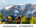 Small photo of Mount Crested Butte Colorado village houses in summer with colorful sunset on green trees and lodging