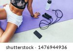Small photo of Cropped shot of a woman in fitness wear relaxing after workout sitting on a yoga mat with mobile phone, water bottle and skipping rope beside her.