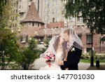 newlyweds embracing in the park | Shutterstock . vector #147701030