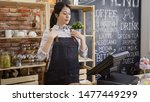 Stock photo beautiful girl seller wearing stylish denim apron at cafeteria job while standing in bar counter 1477449299