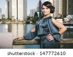attractive young woman standing in front of canal with city skyline  - stock photo