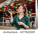 Small photo of Inordinate young woman with dreadlocks hairstyle and fashionable summer clothes throws apple in amusement park.