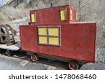 Small red caboose on end of mining rail train.