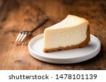 Cheesecake slice, New York style classical cheese cake on wooden background. Slice of tasty cake on white plate served with dessert fork