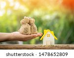 Small photo of Man hand hold money bag with presenting and home model and gold coin with growing interest in the public park, Saving money for buy house or loan for plan business investment of real estate concept.