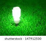 Glowing energy saving light bulb on a green field, energy conservation concept. - stock photo