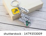 Vestfold, Norway - September, 27, 2019: Keyring GTA 5 on wooden background. Grand Theft Auto (GTA) is a series of computer games and video games. - stock photo