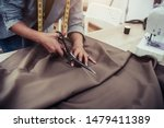 Small photo of Dressmaker cutting dress fabric on sketch line with sewing machine. Fashion designer tailor or sewer in workshop studio designing new collection clothes. Business owner shop and entrepreneur concept