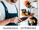 Small photo of cropped view of bearded workman pointing with finger at digital tablet