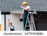 Small photo of selective focus of workman waving hand and looking at coworker standing on ladder with toolbox