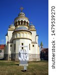 """Small photo of AIUD, ROMANIA - JULY 30, 2019: Back view of the Orthodox Cathedral """"Three Holy Hierarchs"""" with the marble sculpture """"Polyphony"""" by Georgian artist Valerian Jikia."""