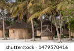 Small photo of Cap Vert peninsula, Senegal - june 28, 2019: Traditional architecture cabins surrounded by palm trees serve as rooms in a hotel near Pink Lake