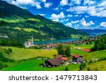 Catholic church, traditional wood and modern houses along the lake Lungernsee in swiss village Lungern, canton of Obwalden, Switzerland