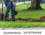 Small photo of A landscape worker digging a trench during an irrigation system installation project in a yard by a quiet residential street