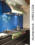 Stock photo blue backsplash and stainless steel vent hood in modern kitchen 148011206