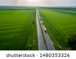 convoys with cargo. trucks on the higthway sunset. cargo delivery driving on asphalt road along the green fields. seen from the air. Aerial view landscape. drone photography. - stock photo
